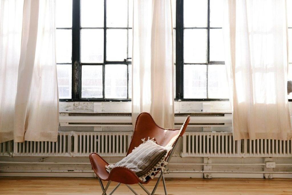 Brązowe krzesło na tle rustykalnych okien